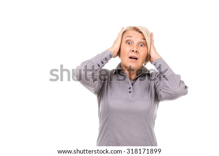 Portrait of senior blonde woman standing isolated on white background. Woman wearing grey blouse. Frightened and shocked woman looking at camera anxiously with hands on head - stock photo