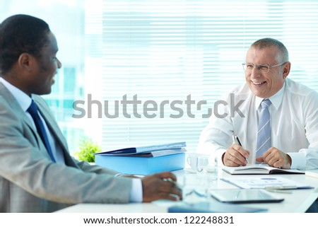 Portrait of senior boss and his employee laughing at meeting - stock photo