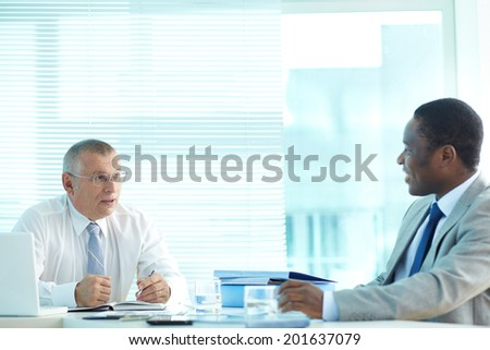 Portrait of senior boss and his employee talking at meeting - stock photo