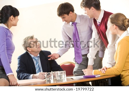 Portrait of senior boss consulting his young colleagues at meeting - stock photo