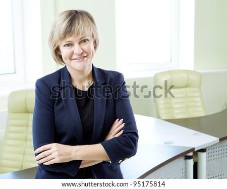 portrait of senior business woman in office interior - stock photo