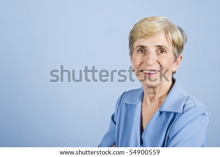 Portrait of senior business woman smiling isolated on blue background ,copy space for text message - stock photo