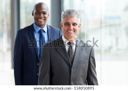 portrait of senior businessman and young african businessman in office - stock photo