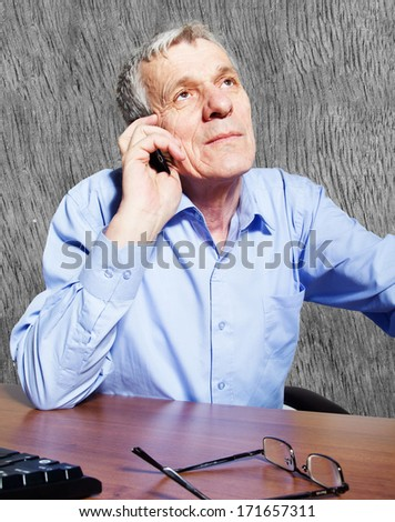 Portrait of senior businessman in office using phone - stock photo
