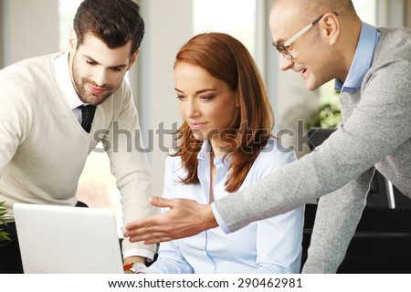 Portrait of senior businessman point out the laptop screen and presenting his idea. Business team consulting at office.  - stock photo