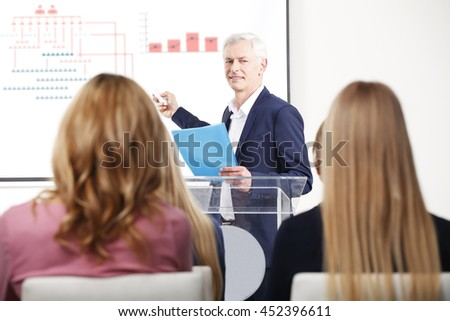 Portrait of senior businessman presenting his financial plan to her colleague in auditorium. - stock photo
