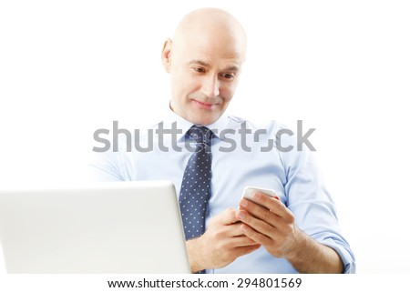 Portrait of senior businessman sitting at desk in front of laptop. Business people holding hands mobile while touching the screen.  Isolated on white background.