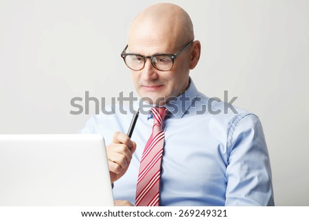 Portrait of senior businessman sitting in front of laptop while holding pen in his hands. Sales man working against white background.  - stock photo
