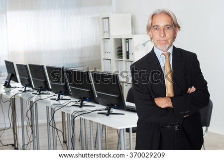 Portrait of senior businessman standing arms crossed in office - stock photo