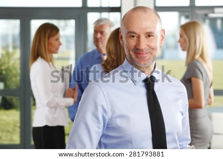 Portrait of senior businessman standing at office while colleagues consulting at background. Teamwork at office. - stock photo