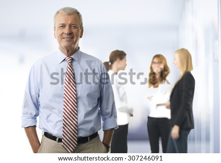 Portrait of senior businessman standing at office while looking at camera and smiling. Businesswomen consulting at background.