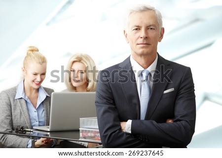 Portrait of senior businessman standing with arms crossed while businesswomen working at background at laptop. Teamwork at office.  - stock photo