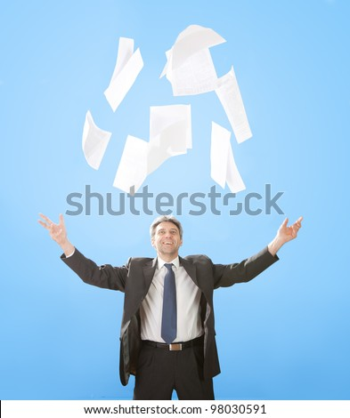 Portrait of senior businessman throwing sheets of paper into the air - stock photo