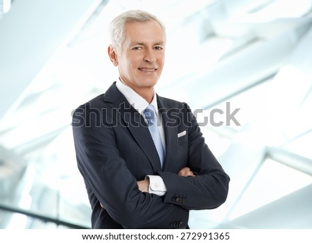 Portrait of senior businessman with arms crossed standing at office while looking at camera. - stock photo