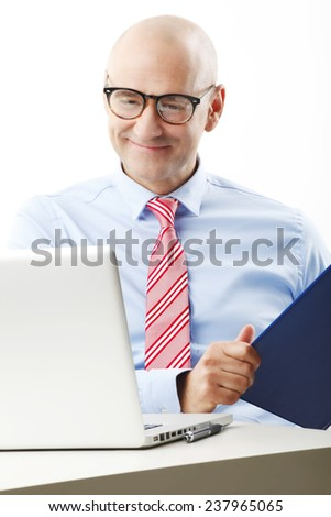 Portrait of senior businessman with laptop working on business strategy while sitting against white background. - stock photo