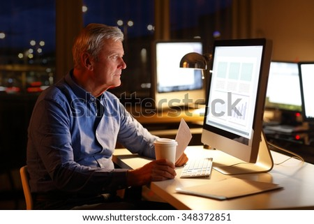 Portrait of senior businessman working on new financial plan while sitting in front of computer late night.  - stock photo