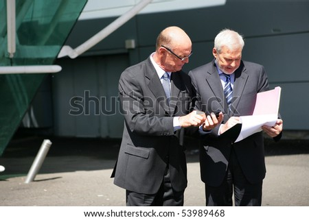 Portrait of senior businessmen with documents and a calculator - stock photo
