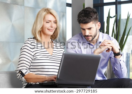 Portrait of senior businesswoman giving advice to young businessman while sitting in front of laptop. Teamwork at office.  - stock photo