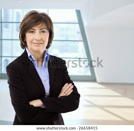Portrait of senior businesswoman standing with arms crossed in office hall, smiling. - stock photo