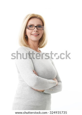 Portrait of senior businesswoman standing with arms crossed while looking at camera and smiling. Isolated on white background.