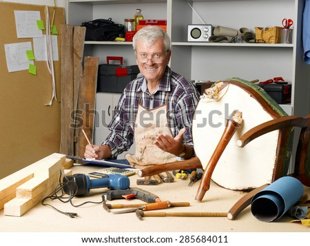 Portrait of senior carpenter holding clipboard and making notes while sitting at his workshop and repair the broken legged chair. Small business at home.  - stock photo