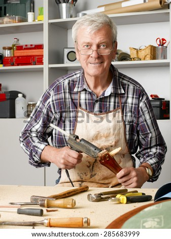 Portrait of senior carpenter sitting at his workshop and repair the broken legged chair. Small business at home.  - stock photo