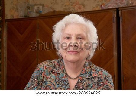 Portrait of senior caucasian woman about ninety years old sitting in her bed room - stock photo