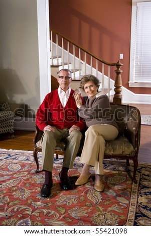Portrait of senior couple at home in living room sitting on sofa - stock photo