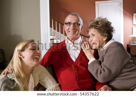 Portrait of senior couple at home in living room with adult daughter - stock photo