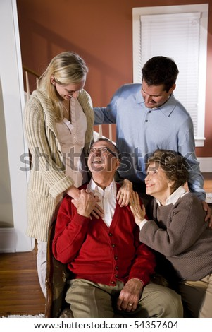 Portrait of senior couple at home on sofa with adult children - stock photo