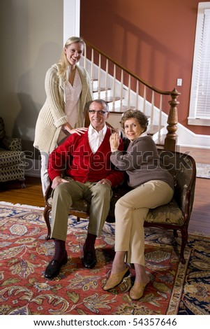 Portrait of senior couple at home on sofa with adult daughter - stock photo