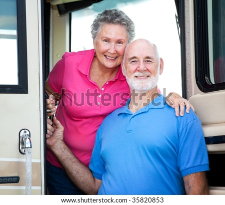 Portrait of senior couple at the door of their luxury RV. - stock photo