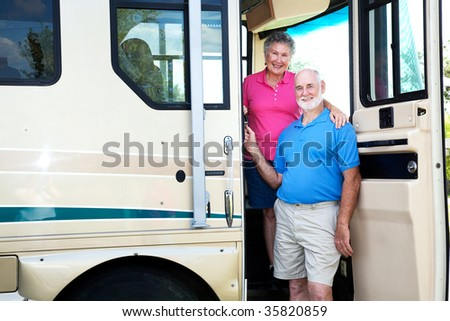 Portrait of senior couple at the door of their recreational vehicle. - stock photo