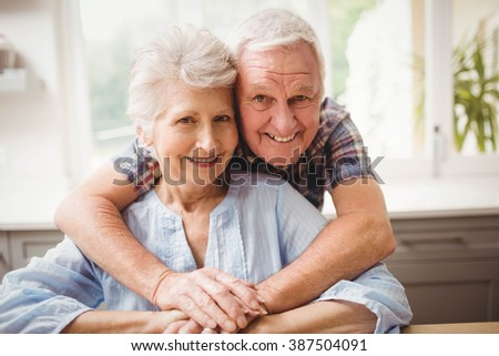 Portrait of senior couple embracing at home - stock photo