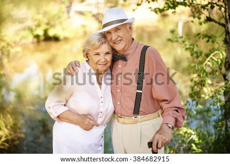 Portrait of senior couple embracing outdoors - stock photo