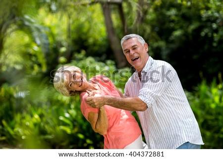 Portrait of senior couple enjoying while dancing in yard - stock photo