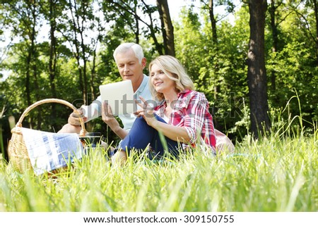 Portrait of senior couple having picnic in the forest. Elderly woman holding hand digital tablet and sitting next to her old man and reading the map online together on the tablet.  - stock photo