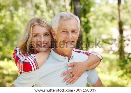 Portrait of senior couple hiking in the forest. Elderly woman embracing her senior man while standing outdoors and spending time together.  - stock photo