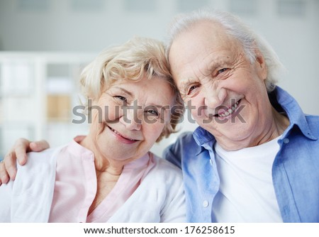 Portrait of senior couple looking at camera with smiles - stock photo