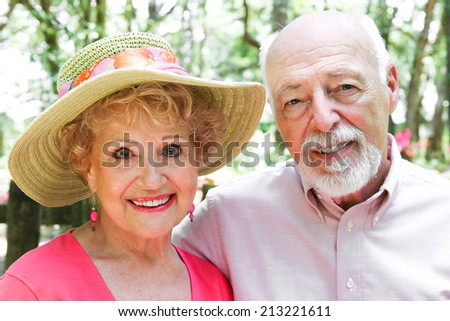 Portrait of senior couple outdoors in park-like setting.   - stock photo