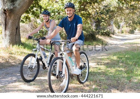 Portrait of senior couple riding cycle in the park. Happy mature couple wearing helmet and cycling. Retired senior man and smiling woman riding a bike and looking at camera