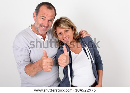 Portrait of senior couple showing thumbs up - stock photo