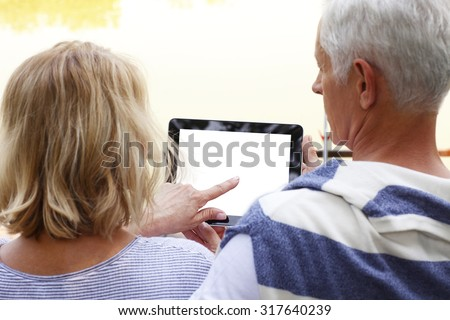 Portrait of senior couple sitting at lakeside. Elderly woman holding hand white blank screen digital tablet while old man sitting next to her and looking the display. - stock photo