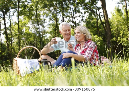 Portrait of senior couple sitting at the woods and drinking tea while take an excursion.  - stock photo