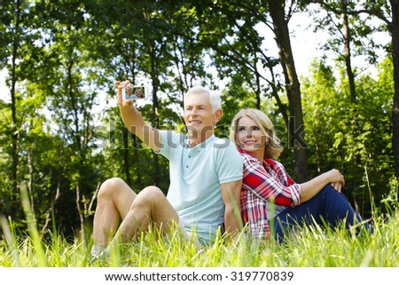 Portrait of senior couple sitting in the forest and relaxing. Elderly man holding in his hand mobile phone and taking self portrait while retired woman sitting next to him.