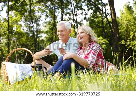 Portrait of senior couple sitting in the forest while relaxing and drinking a cup of tea. - stock photo