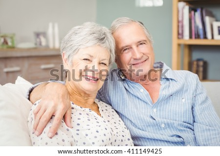 Portrait of senior couple sitting on sofa at home - stock photo