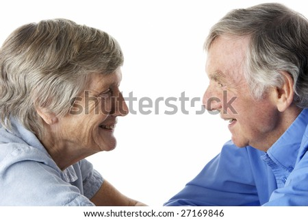 Portrait of senior couple smiling at each other - stock photo