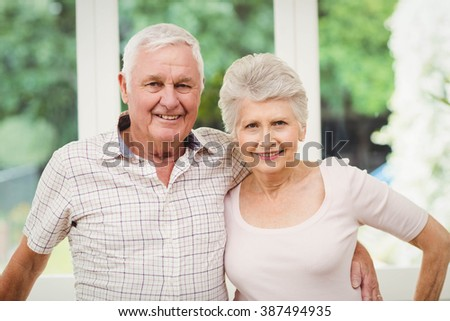 Portrait of senior couple smiling in kitchen at home - stock photo