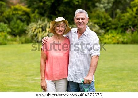 Portrait of senior couple standing at yard - stock photo
